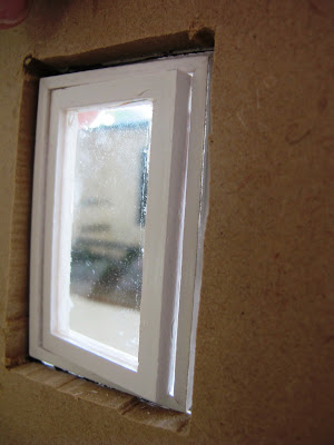 Close up of the Inside of a half-built dolls' house shed, showing that the windows don't fit the full depth of the wall.