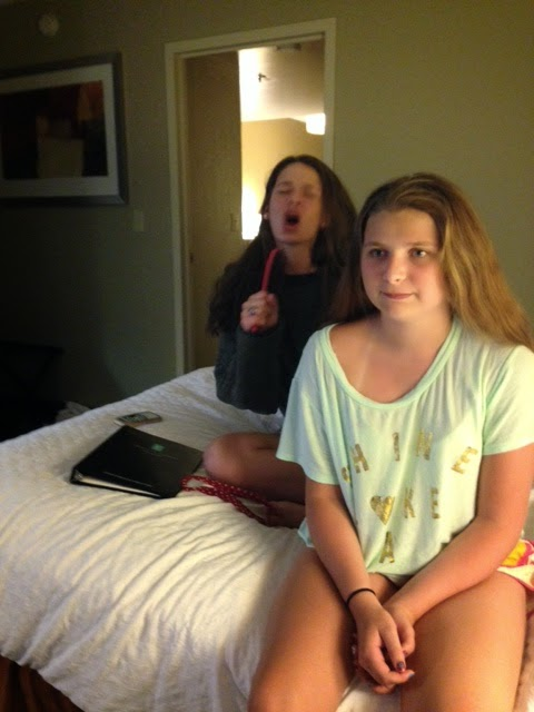 Girls watching fireworks from hotel window and one singing into a hairbrush