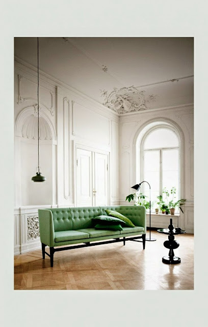 large open and  airy white living room with green velvet sofa