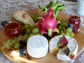 Luxurious cheese platter, with brie, grapes, pickle and more - decorated with flowers and on a wooden cheeseboard.