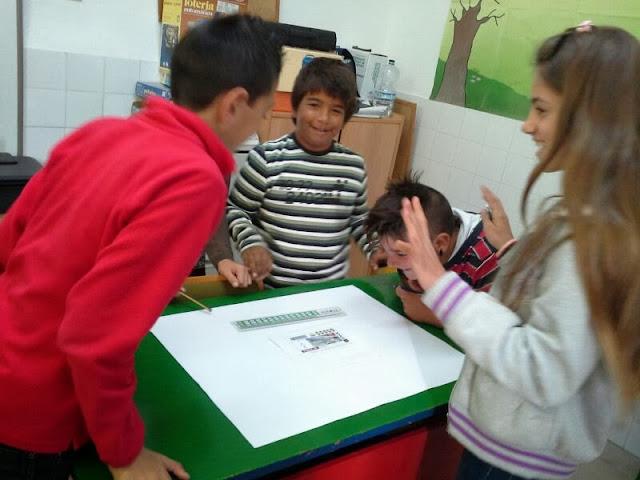 En la imagen se ven a tres alumnos trabajando sobre un mural en blanco y un cupón de la ONCE como modelo
