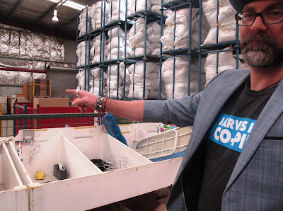 A man points out something in front a sorting bins and a pallet rack full of large bags of clothing.