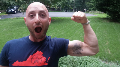 Benjamin Rubenstein with new inner bicep tattoo of fig tree and droplets of green water