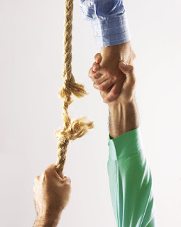 Picture of man's hands being aided when he is at the end of a breaking rope.