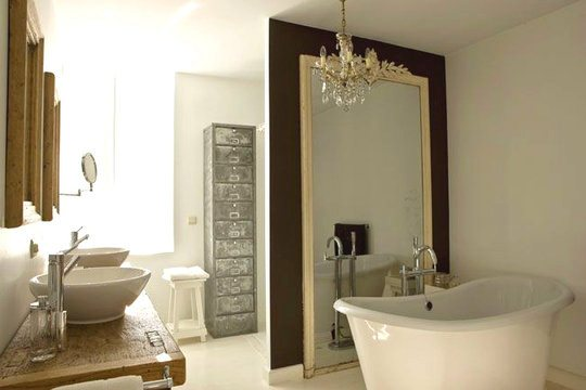 Bathroom in mansion with stand alone tub, chandelier, traditional mirror next to tub and bowl sinks