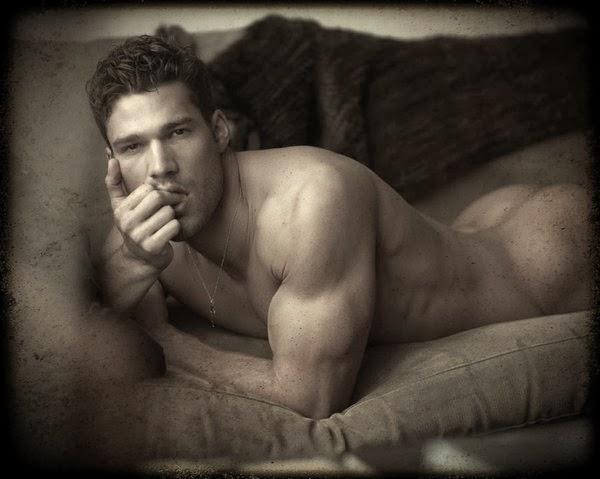 Homme nu allongé sur canapé regardant langoureusement