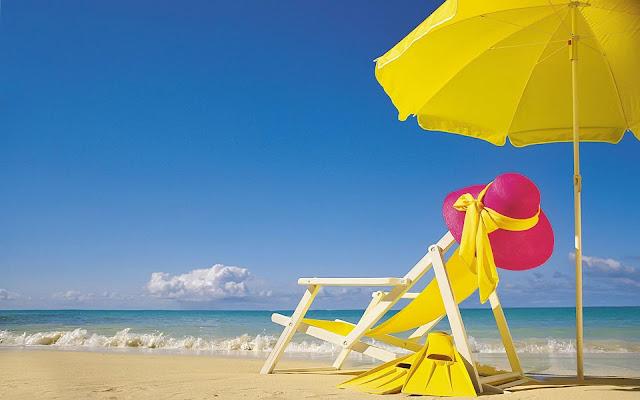 Wwitte strandstoel en gele parasol op het strand