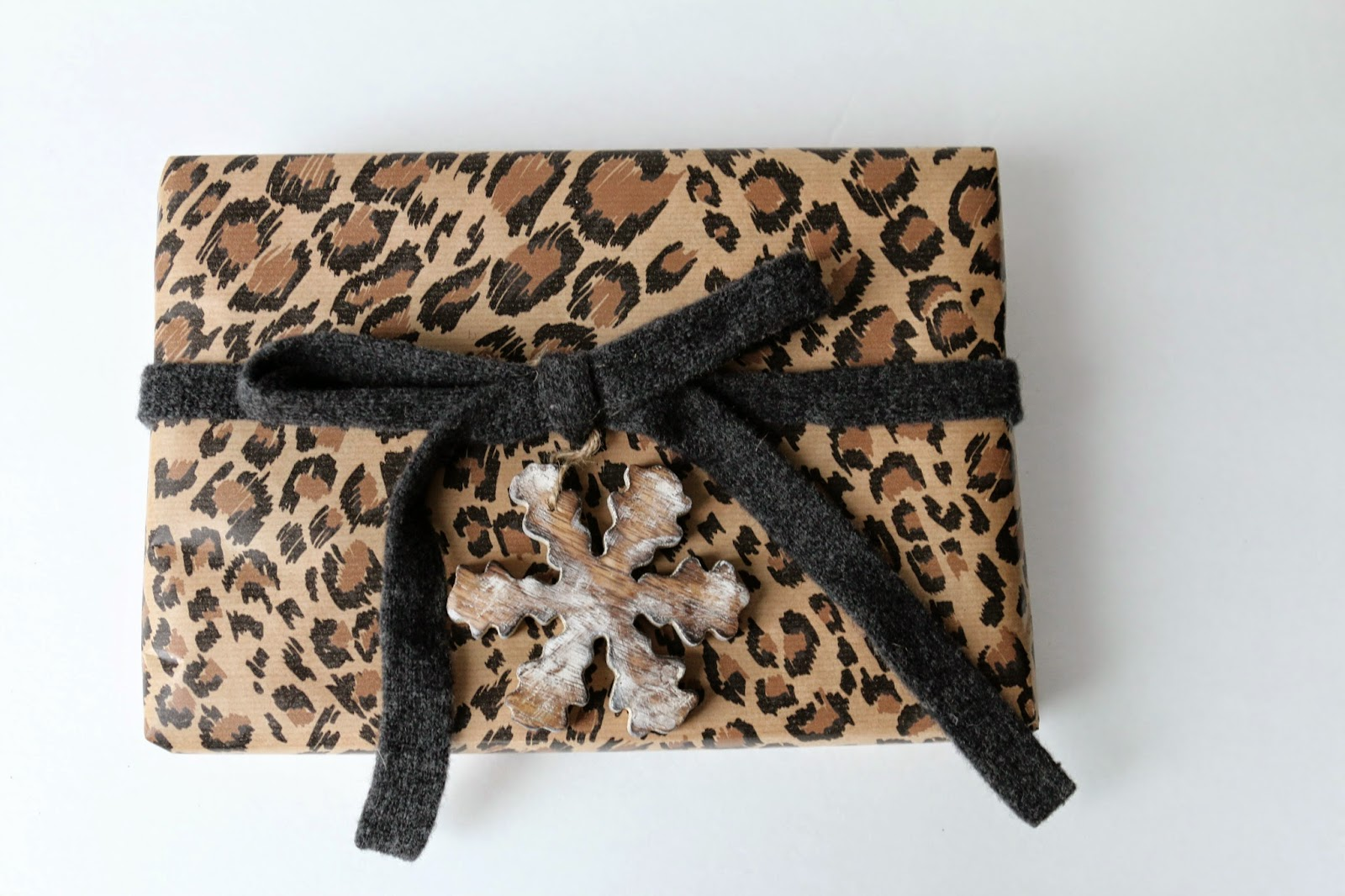 Holiday gift wrapping with animal print paper and wood ornaments