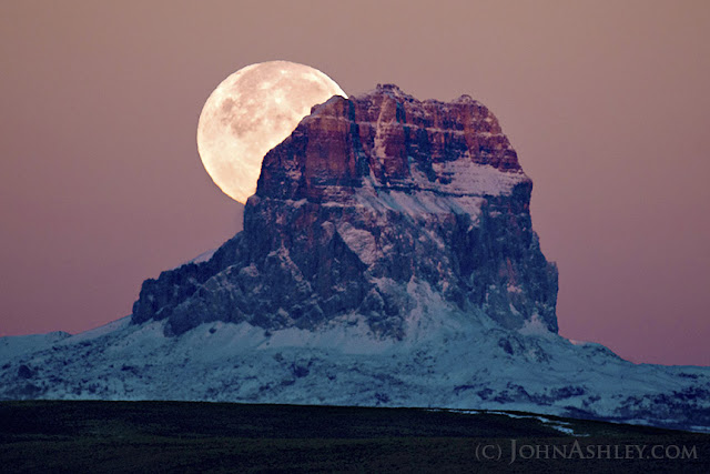 Hunters' Moon behind Chief Mountain (c) John Ashley