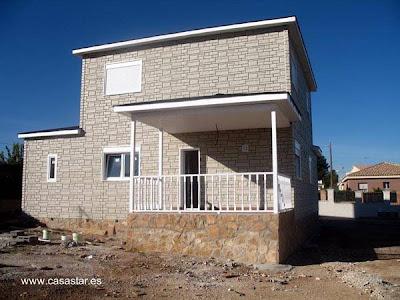 Casa de madera cubierta de una terminación símil piedra en España