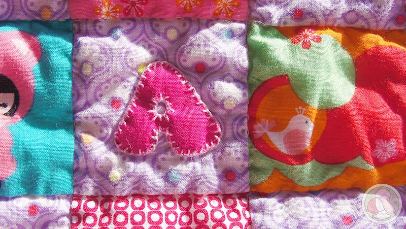 Colcha de cuna de patchwork con letras aplicadas