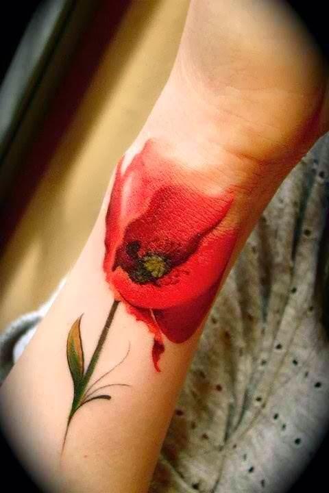 Red poppy flower tattoo on arm