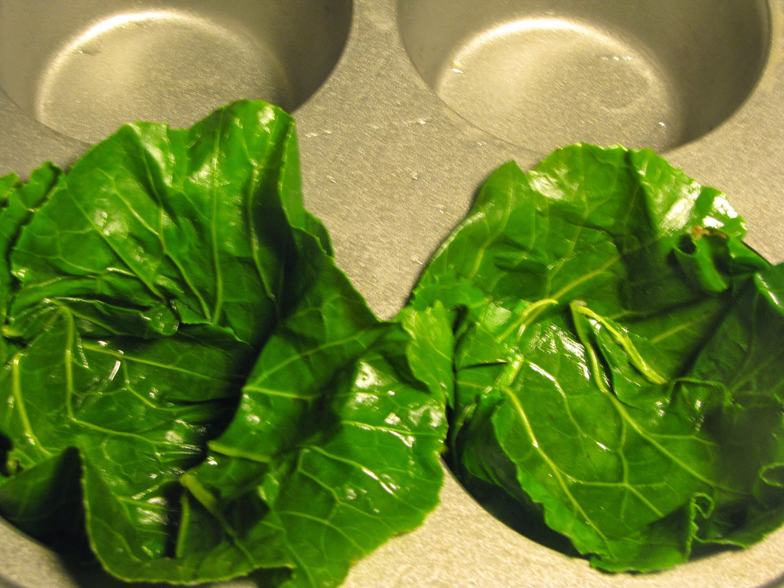 Collard green leaves drapes into a cupcake pan