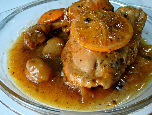 Primer plano de la rodaja de naranja sobre el pollo y diente de ajo