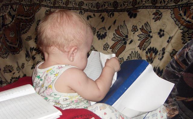 Маленький ребенок читает книгу сказок