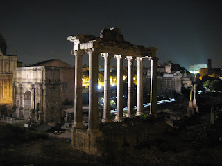 Roman Forum lit up at night with the Colosseum visible in the distance.