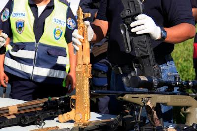 SEORANG anggota polis menunjukkan selaras senjata api AK-47 bersalut emas yang dihiasi batu berlian dan zamrud di Ciudad Jardin de Choloma pada Sabtu lalu.