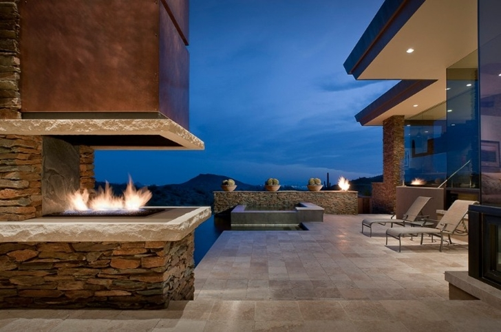 Outdoor fireplace in Modern desert home by Tate Studio