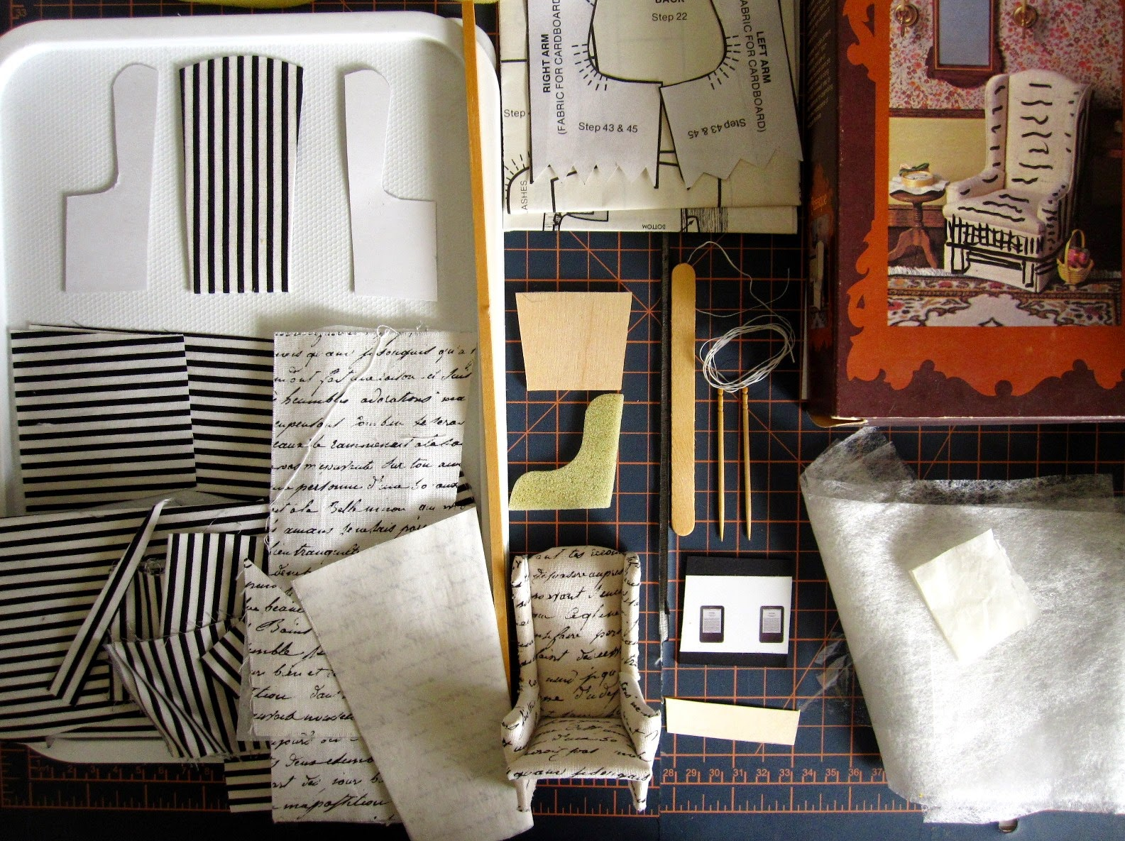 Pieces of a dolls' house miniature wing chair kit arranged on a cutting mat.