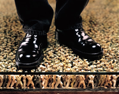 side view of person's feet on the floor of figures holding up floor