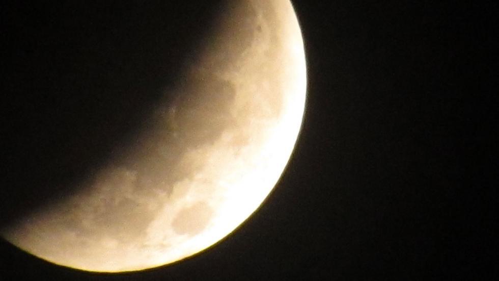 Луна частично окутана тенью Земли в начале затмения