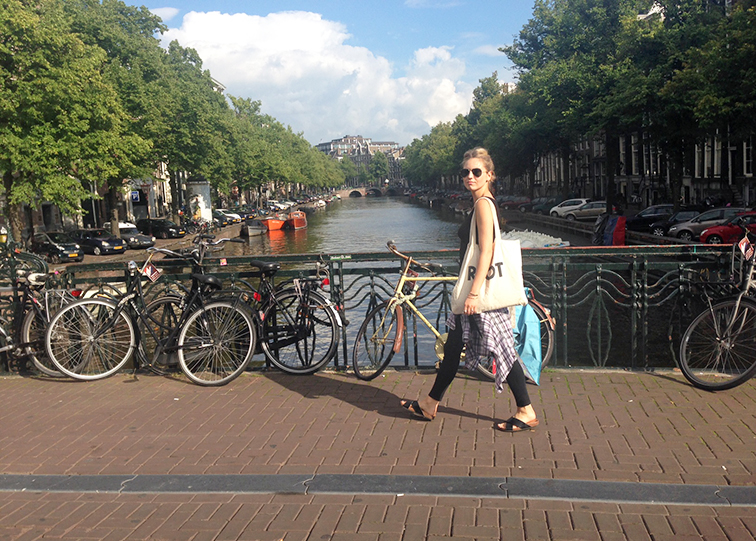 Fashion Over Reason in Amsterdam, crossing a canal, in motion, plaid and black, summer day
