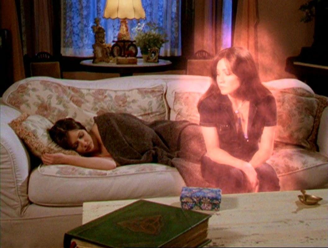 Mujer durmiendo en sofá y a su lado su doble energético sentada mirándola