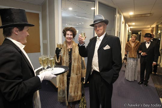 L-R: Eve Vernik-Taaffe, events assistant from the Art Deco Trust, serving drinks to Shelley Verran and Bill Hayes from Tauranga, at the Grand Anniversary Ball, the weekend opener of the Winter Art Deco celebrations, at the Napier War Memorial Conference Centre, Napier. photograph