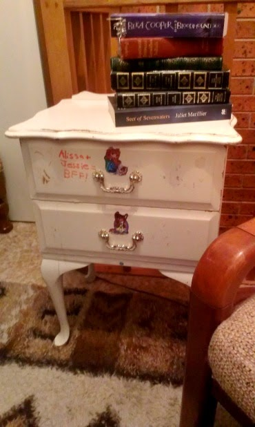 Small white vintage bedside table  with stickers and writing on the drawers, next to a reading chair, with a pile of books on top.