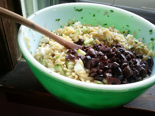 Orzo salad with addition of kalamata olives, ready to be combined.