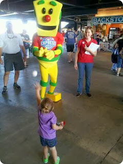 A young girl waves to a mascot promoting internet safety.