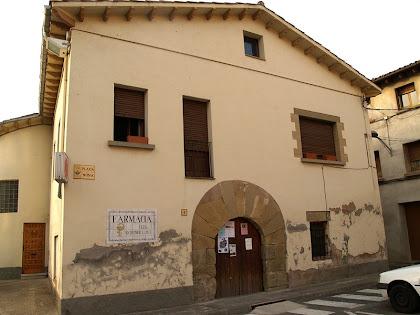 La farmàcia del poble amb la porta d'entrada de l'antiga rectoria