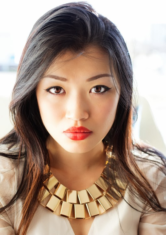 Vancouver Fashion blogger Jasmine Zhu close up wearing chunky gold necklace from community thrift and vintage
