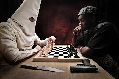Hvid Ku Klux Klan mand spiller skak mod sort mand, mens våben ligger på bordet