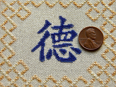 "Detail of ""virtue"" Chinese character block, with penny shown for scale"