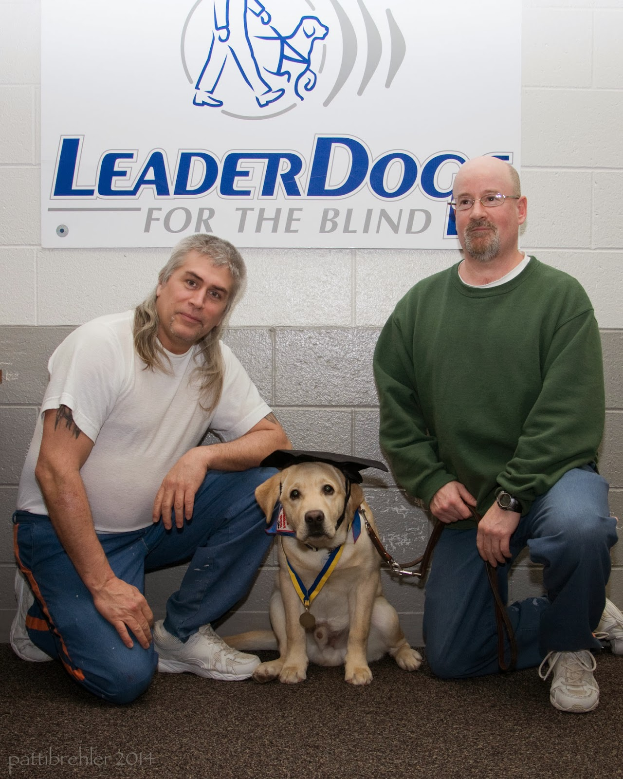 Two men are kneeling on one knee with a golden retriever between them. The man on the left is wearing a white t-shirt and blue pants. The man on the right is wearing a green sweatshirt and blue pants. Behind  them on the wall is a white poster with Leader Dogs for the Blind written on it. The dog is wearing a black graduation cap and a yellow and lbue ribbon with medal around its neck.