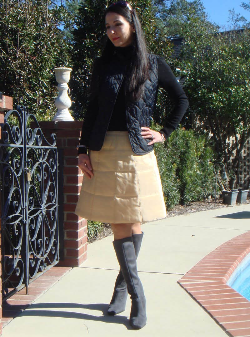 Wearing a quilted vest, black long sleeve turtleneck, quilted gold skirt and knee high grey suede boots.