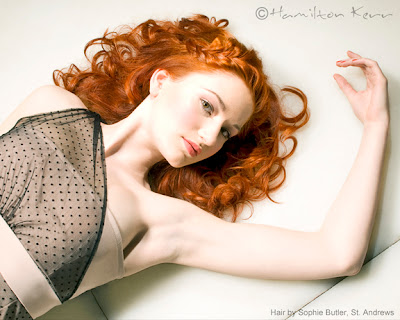 Reclining redhead model with pale skin and red lipstick on a white background. Red, ginger, beautiful