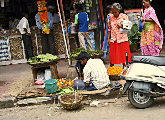 man selling flowers on pavement