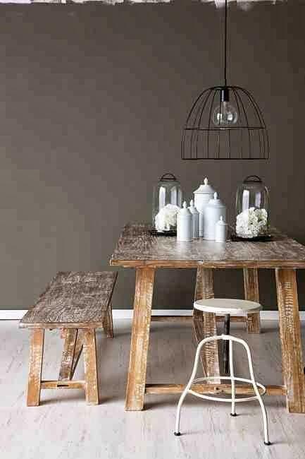Drewniany stół, drewniana ławka, metalowy taboret, rustykalno-industriana aranzacja, szara ściana