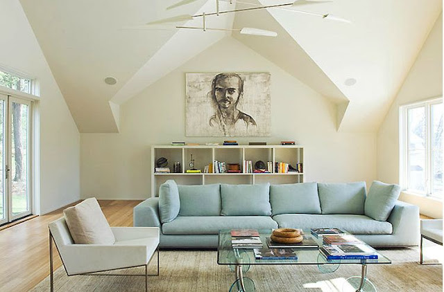 Living room with long light blue sofa, a white arm chair, glass coffee table, wood floor, a white cubby style book shelf with a large portrait above it
