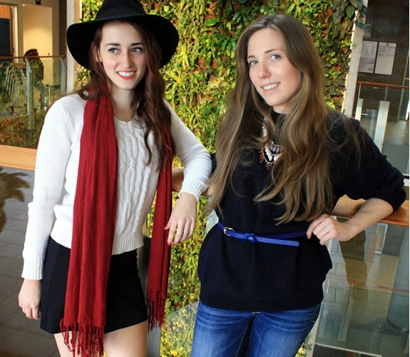 two students pose in front of the living wall