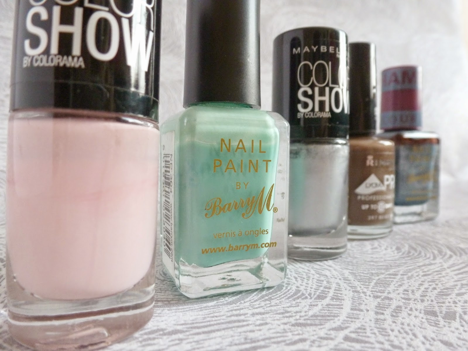 Nail varnishes in a row. Maybelline colour show in the colours 107 watery waste and 77 nebline. Rimmel London's lycra pro in 297 beige babe. Barry M in 304 mint green. Barry M chameleon range in 331 chameleon blue