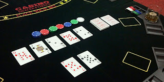 poker table showing an inside straight 7,8,9,10, jack with poker chips and a drink