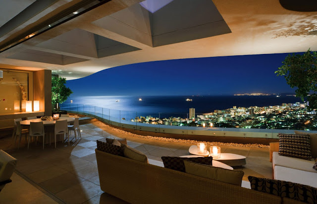 Picture of the city and the ocean as seen at night from the mansion