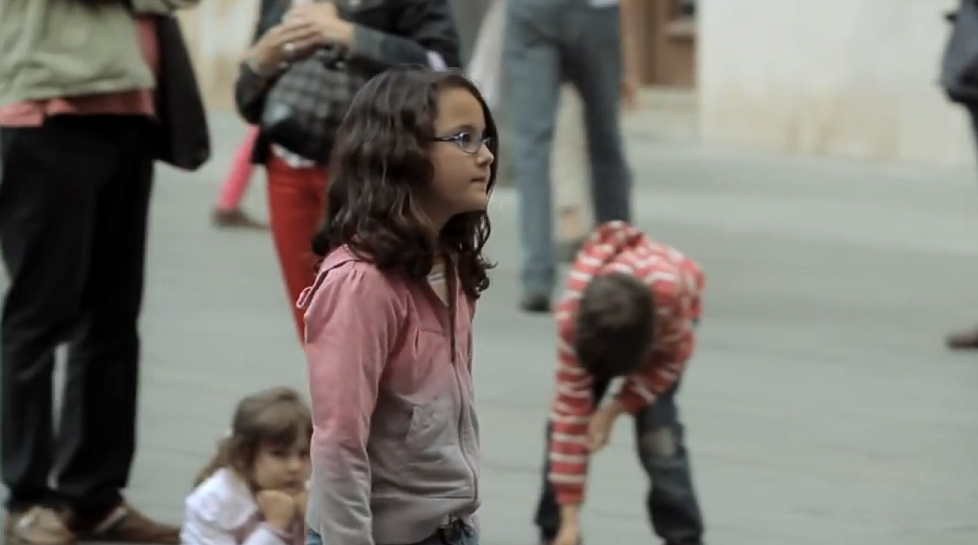 girl giving charity to street performer