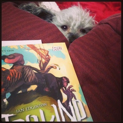 Murchie's face is barely visible above a red comforter. In front of him sits a trade paperback copy of the first volume of Hinterkind.