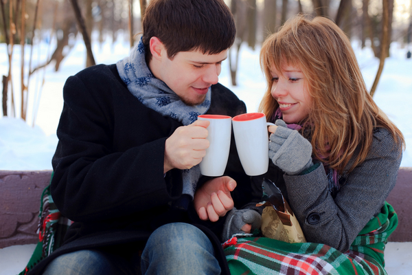 A couple snuggle closely and toast their hot chocolate outside on a snowy day.