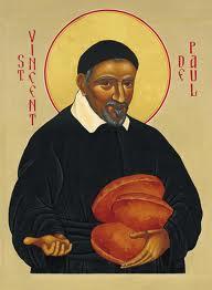 San Vicente sonriendo lleva panes en una mano y con la otra pide caridad
