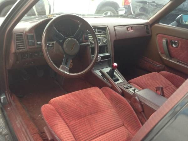 1985 mazda rx7 interior. inside a garish sophisticated red interior greets the driver and reminds him that there was time when auto manufacturers made brothel cloth interiors 1985 mazda rx7